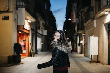 Spain, Reus, portrait of smiling young woman walking at pedestrian area in the evening