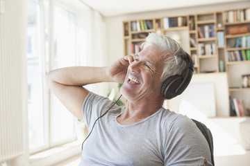 Portrait of relaxed man hearing music with headphones at home