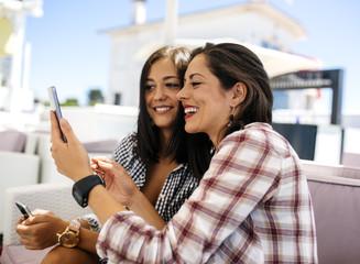 Two happy female friends on terrace taking a selfie
