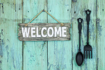 Welcome sign hanging on mint green background by cast iron spoon and fork