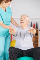 Senior auf Gymnastikball bei der Physiotherapie