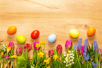 Wooden background with spring flowers and easter eggs