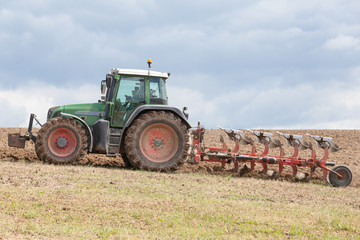 Farmer ploughing, or plowing,  a field preparing the soil for the planting of the spring crop with a tractor and plough