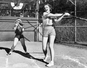 Two women playing baseball