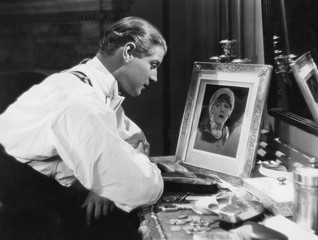 Man looking at portrait of woman