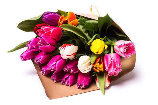 Bouquet of spring multicolor tulips flowers wrapped in present paper  isolated on white background
