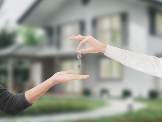 Mani con chiavi casa sfondo giardino