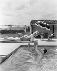 Young woman lying on a diving board with a young man hanging from it