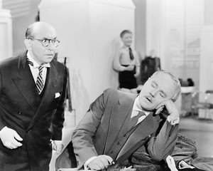 Man looking shocked at a sleeping businessman in the office