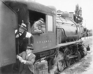 Three men waiting at a steam locomotive