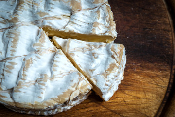 SLice of camembert cheese rustic wooden table