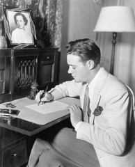 Man sitting at his desk writing a letter with a fountain pen