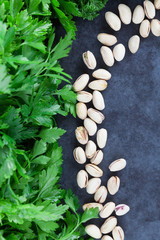 Curly-leaf and flat leaf parsley with pistachios on grunge background with copy space. Top view.