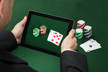 Poker Hand With Digital Tablet Showing Chips And Cards