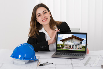 Female Architect Showing Picture Of House On Laptop
