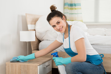 Female Housekeeper Cleaning Nightstand