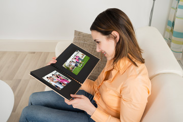 Happy Young Woman Looking At Photo Album