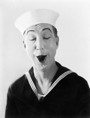 Man in sailor hat and uniform making a silly pantomime face