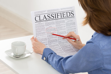 Businesswoman Highlighting Advertisement On Newspaper