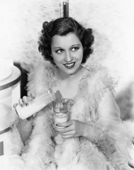 Young woman wearing a feather boa pouring milk into a glass and smiling