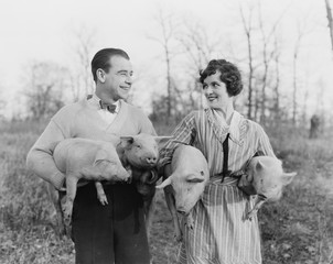 Couple carrying pigs