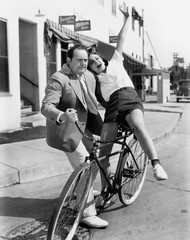 Man trying to balance an exuberant woman on a bicycle