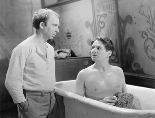 Two men talking while one sitting in a bathtub