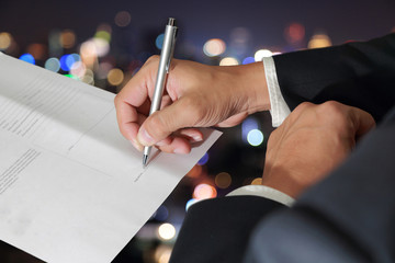 Businessman's Hand holding a pen signing to the document on blurred abstract night bokeh background as Approval Concept.