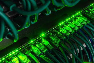 Close up of green network cables connected to switch glowing in the dark