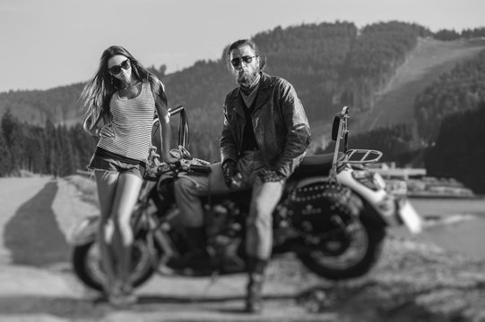 Couple standing by a motorbike. Handsome man wearing leather jacket, gloves and boots and young beautiful sexy woman wearing shorts. Summer day. Tilt lens blur effect. Black and white