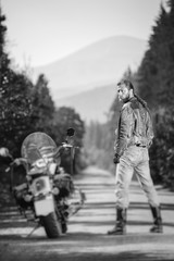 Biker with long hair standing near his custom made cruiser motorcycle on the open road. Looking to the camera. View from the back. Tilt shift soft effect. Black and white