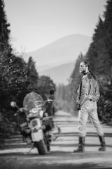 Handsome biker with long hair wearing leather jacket, jeans, boots and gloves standing near his custom made cruiser motorcycle on the open road. Looking to the sun. Tilt soft effect. Black and white