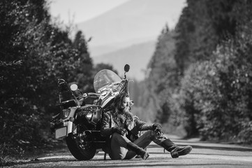 Handsome biker with beard and long hair sitting next to a traveler motorcycle on an open road. Sunny summer day in the mountains. Tilt shift soft effect. Black and white