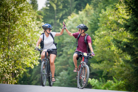 Young couple ride on a mountain asphalt road in the woods on bikes with helmets giving each other a high five