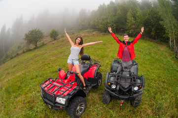 Happy beautiful couple standing on four-wheelers ATV smiling and holding thier hands up. Wide view from high piont