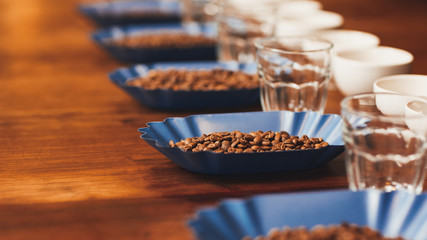 Row of containers with roasted coffee beans on table