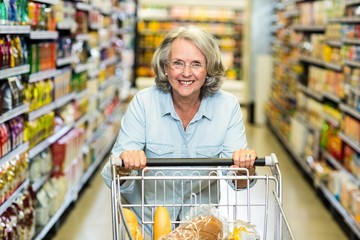 Smiling senior woman with cart