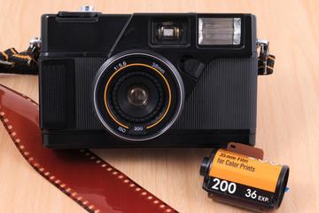 Old camera, vintage camera films popular in the past on wooden desk table.