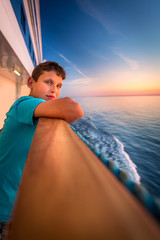 Boy at the railing of a cruise ship at beautiful sunset.