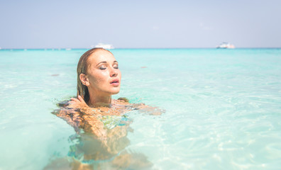 Woman swimming in blue tropical water