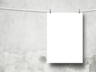 Close-up of one hanged paper sheet with pegs on scratched concrete wall background