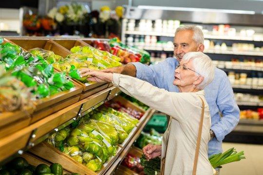 Smiling senior couple buying apples