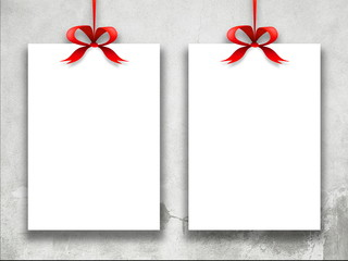 Close-up of two hanged paper sheets with red ribbons weathered wall background