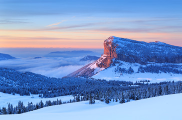 Fotomurales - Winter forest on mountain range in French Alps during a colorful sunset.