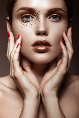 Beautiful girl with a gentle make-up and crystals on the face.