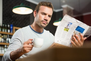 Handsome man reading newspaper and having a coffee