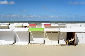 Strandhütten in Blankenberge, Belgien, eine Frau genießt die Sonne in ihrem Liegestuhl.