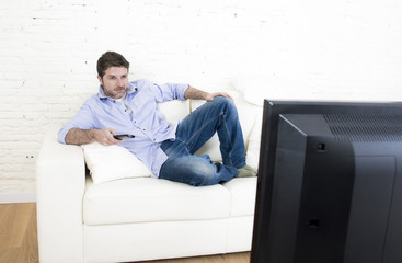 young happy man watching tv lying at home living room sofal looking relaxed enjoying television