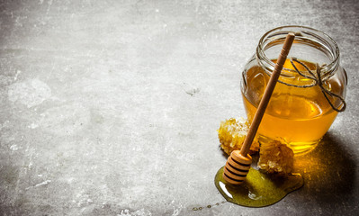 Wall Mural - Glass jar with honey . On stone table.