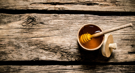 Natural honey in wooden barrel with spoon.